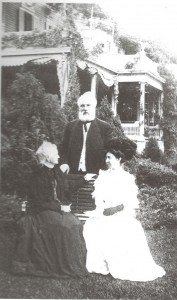 Alexander Graham Bell standing, seated on the left his mother-in-law Gertrude McCurdy Hubbard and his wife, in white, Mabel Bell. The Twin Oaks house is behind them. (Courtesy of the Grosvenor Collection of the Library of Congress)